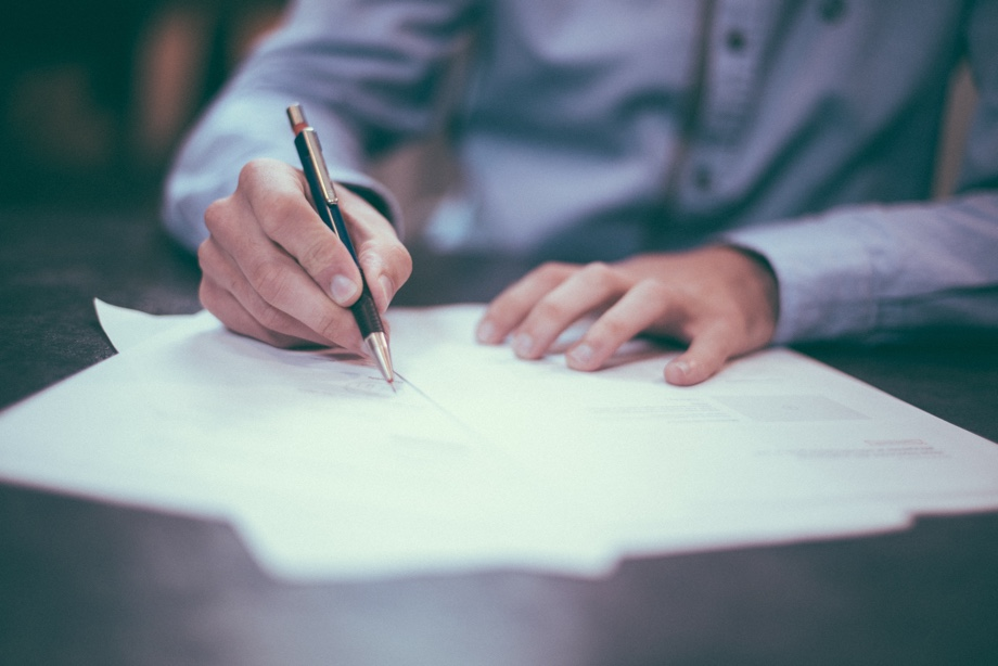 A man using a pen to sign a document